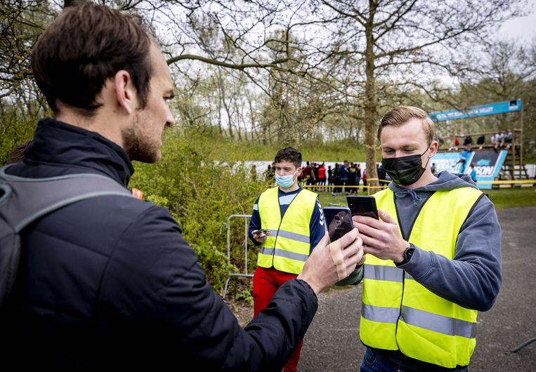 Een medewerker van een 'fieldlab' controleert een testcertificaat.  Beeld EPA