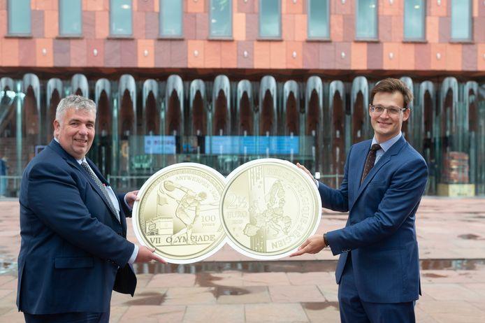 Peter Wouters (N-VA) en Antwerpenaar Vincent Van Hecke, topman van de Nederlandse Munt, tonen de voor- en achterzijde van de Olympische munt, weliswaar fors uitvergroot.