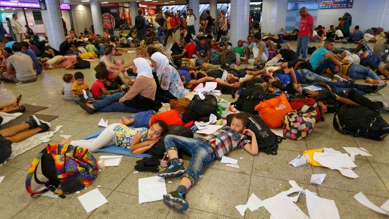 Migranten rusten uit in een metrostation in Boedapest, vlakbij een treinstation waar hen de toegang werd ontzegd. Beeld REUTERS