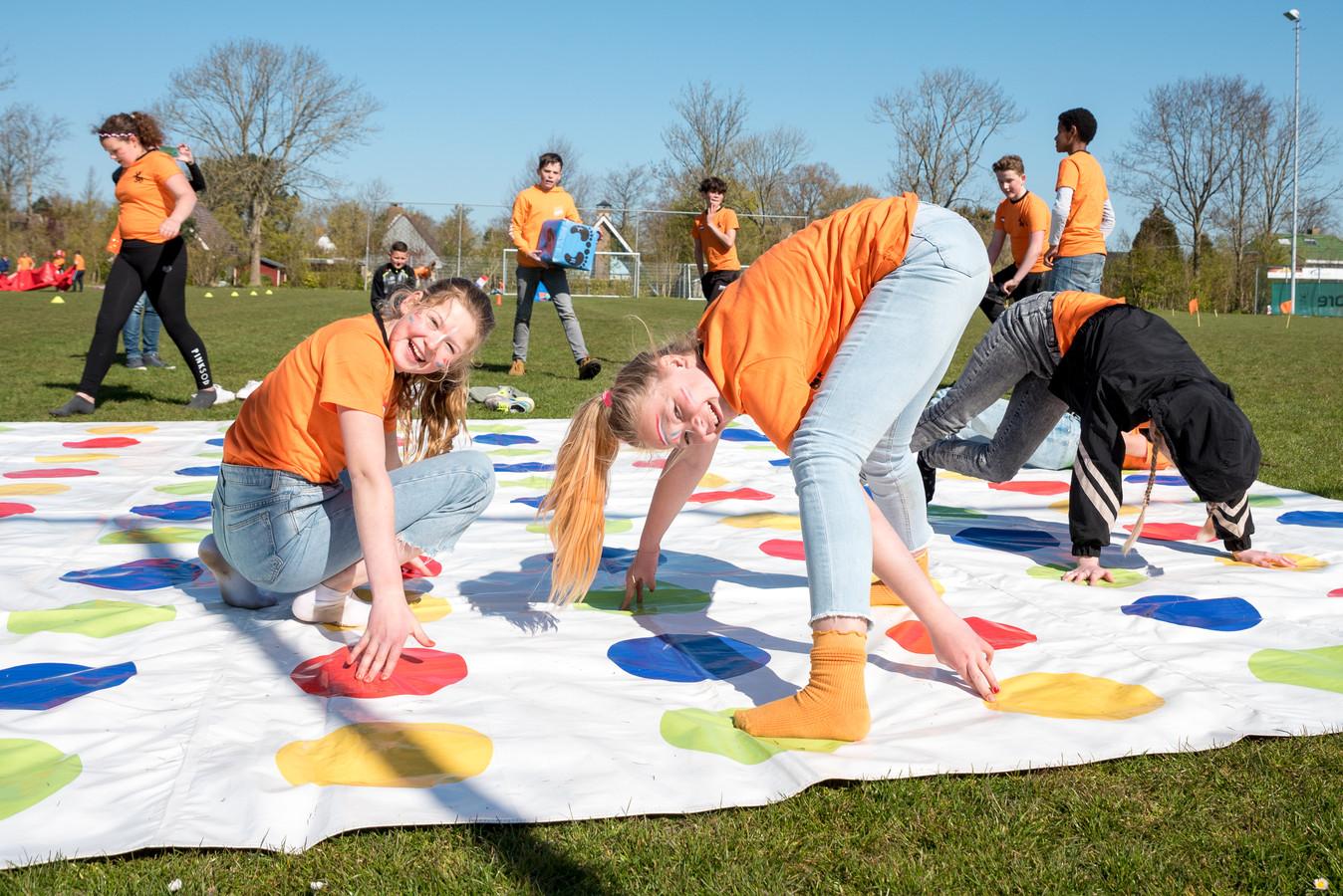 Leerlingen Jasmijn Noordzij, Mechteld Vlam en Maud Mulder (vlnr) houden het het langste vol op met reuzentwister tijdens de koningsspelen op het terrein van voetbalclub Z.S.C. in Scharendijke.