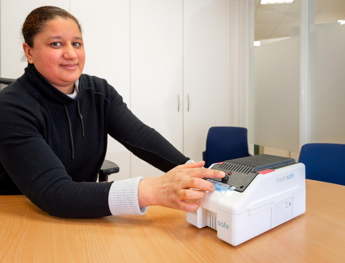 Apotheker Fatima El Bouzidi van het ETZ in Tilburg demonstreert de Meds Safe. Door op de knop te drukken, komt één pil beschikbaar voor de patiënt. De medicijnkluis zou medicijnverspilling tegen moeten gaan.