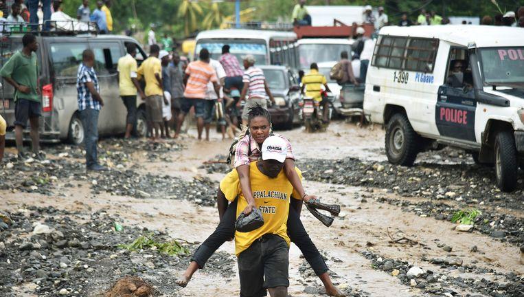 Haïtianen steken een rivier over in Petit Goave, waar een brug is ingestort. Beeld afp