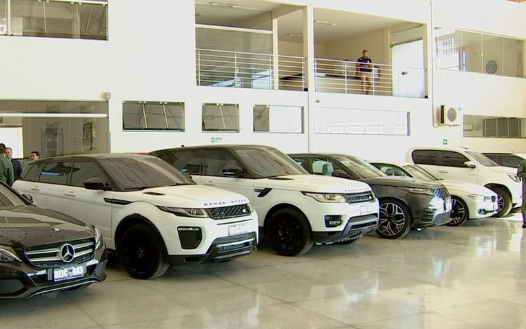 Een aantal van de in beslag genomen luxe auto's die de bendeleden gebruikten.  Beeld Polícia Civil/Goiás