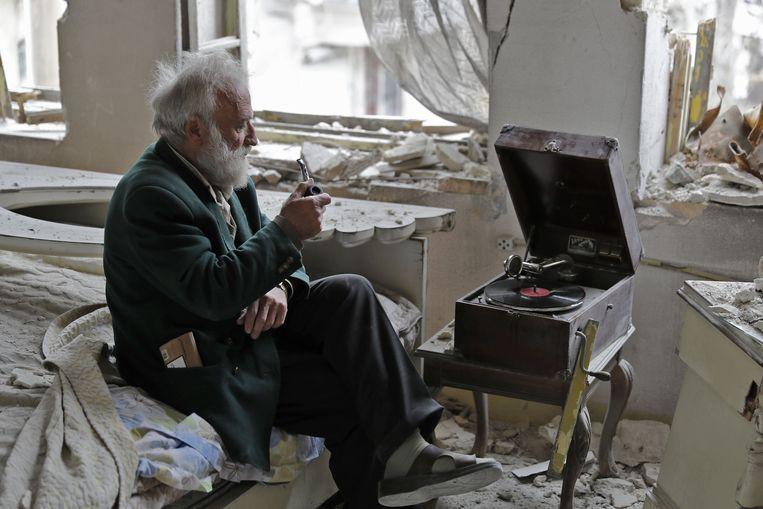 Mohammad Mohiedin Anis, 70, rookt zijn pijp terwijl hij in zijn verwoeste slaapkamer luistert naar zijn platenspeler.  Beeld AFP