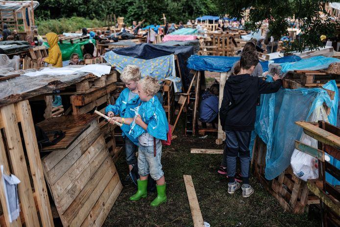 Regen? De kinderen timmeren gewoon verder aan het dorp van pallets in Zevenaar.