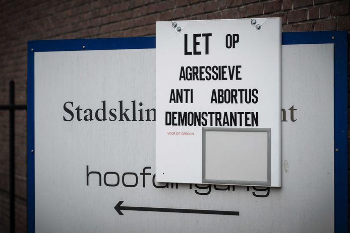Voor de deur van een abortuskliniek in Utrecht hangt een bord waarmee wordt gewaarschuwd voor agressieve anti-abortusdemonstranten.