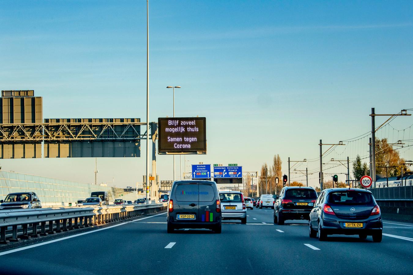 Op borden boven de snelweg prijkt de boodschap 'Blijf zoveel mogelijk thuis'.