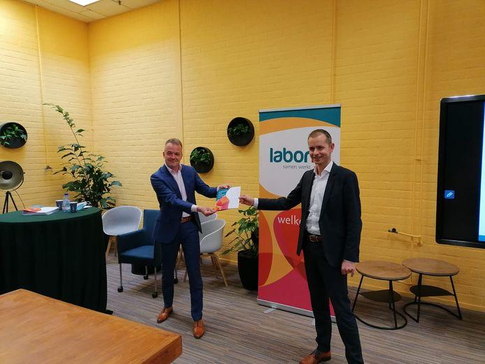 Wethouder Huizinga neemt de brochure in ontvangst van adjunct-directeur Spruit van Laborijn.
