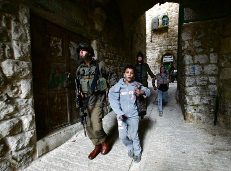Israëlische soldaten voeren jonge stenengooiende Palestijnen mee in Hebron. (FOTO AFP ) Beeld AFP