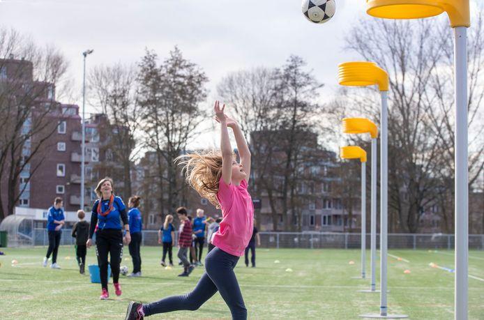 Een meisje maakt kennis met korfbal tijdens een clinic bij KV Wageningen.