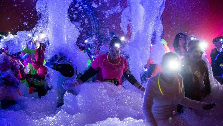 Tijdens Glow in the Park in het Amstelpark moet je onder andere door een gigantische schuimpartij. Beeld Glow in the Park