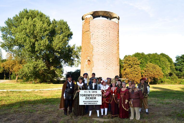 De leden van vzw De Maagdentoren in vol ornaat aan de donjon.