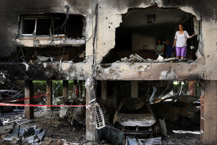 Bewoners van de stad Petah Tikva nemen de schade op na een raketaanval van Hames.