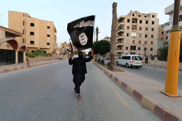 Een IS-militant zwaait met een kalasjnikov en een IS-vlag in de Syrische stad Raqqa in 2014. In Turkije worden nu geregeld strijders van IS gearresteerd. Beeld Reuters