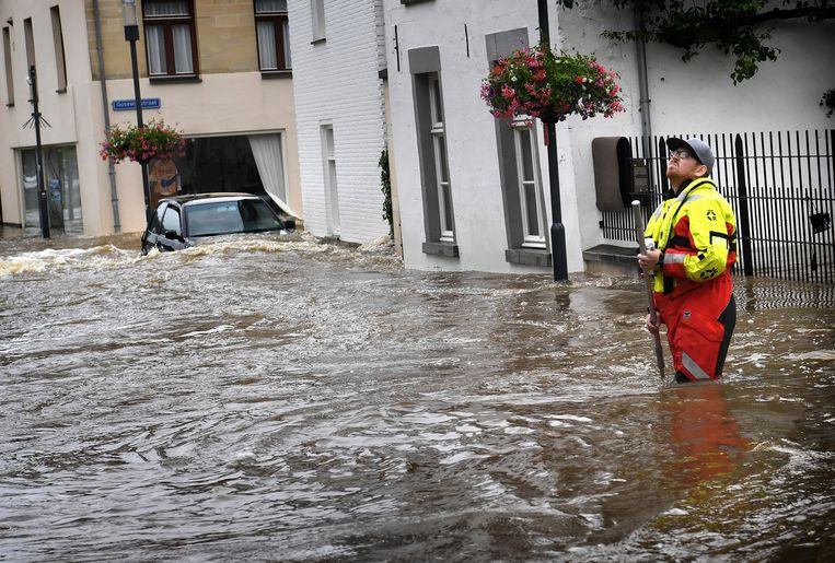 Het centrum van Valkenburg is door de overstroming van de Geul veranderd in een kolkende watermassa. Een lid van de reddingsbrigade speurt de huizen af om te kijken of er nog mensen zitten.  Beeld Marcel van den Bergh / de Volkskrant