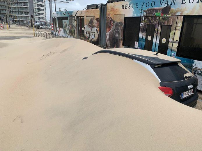Een auto, verstopt in het zand.