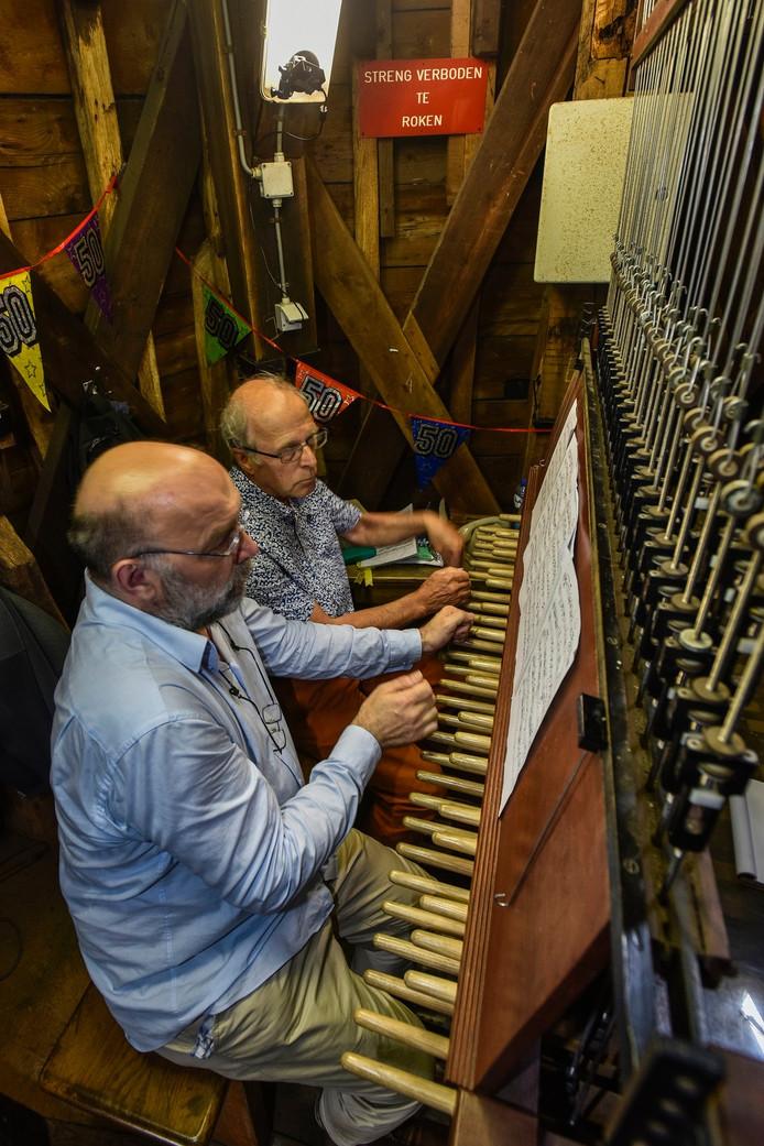 Carl Van Eyndhoven (l) is de nieuwe beiaardier van de Heikese Kerk. Hier speelt hij samen in de torenspits met de oude beiaardier Arie Abbenes.