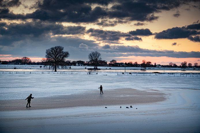 Kinderen schaatsen tussen Alphen en Maasbommel op het ijs.