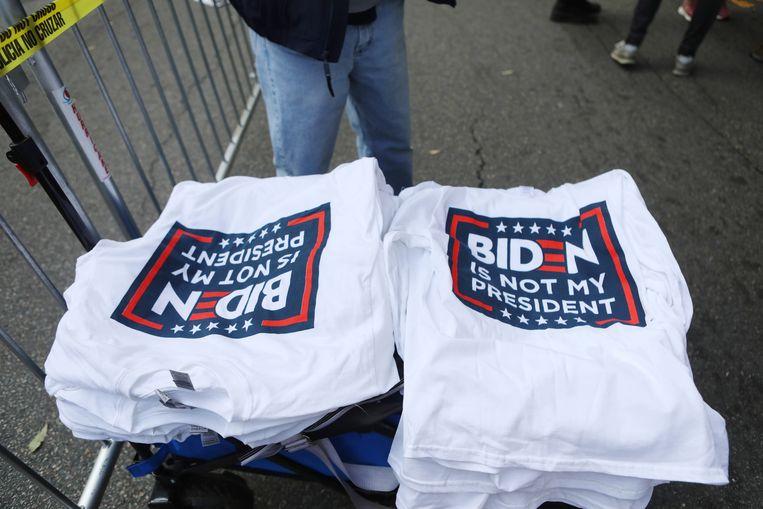 Bij de protesten van aanhangers van president Trump probeert een verkoper zaken te doen met anti-Biden-T-shirts. Beeld REUTERS