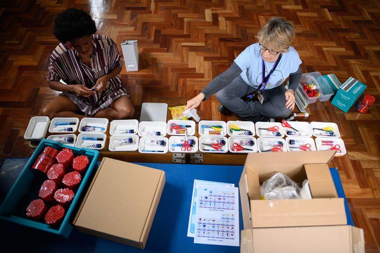 Assistent Kathy Hammond (rechts) en lerares Muriel Thompson (links) maken pakketjes met kantoorartikelen voor kinderen van de Muswell Hill Basisschool in Londen.  Beeld Getty Images