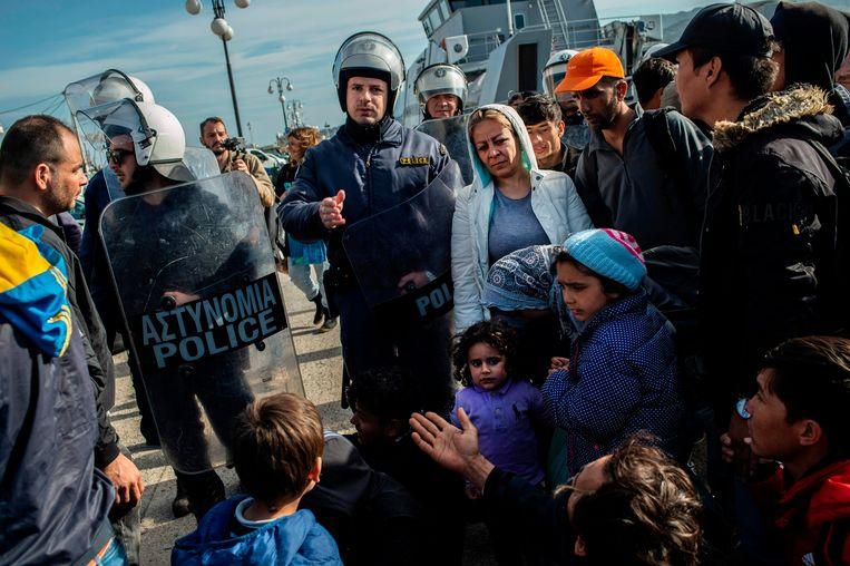 Oproerpolitie houden migranten tegen nabij de haven van Lesbos. Beeld AFP