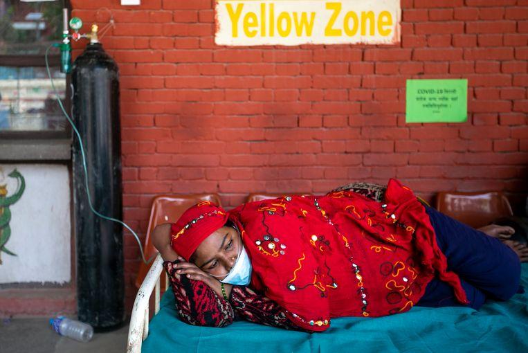 Een Nepalese vrouw krijgt zuurstof in afwachting van haar testresultaat buiten de spoedeisende hulp van een ziekenhuis in Kathmandu, Nepal. Beeld AP