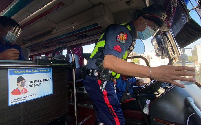 Een Filipijnse politieagent inspecteert de handgel in een taxibusje.