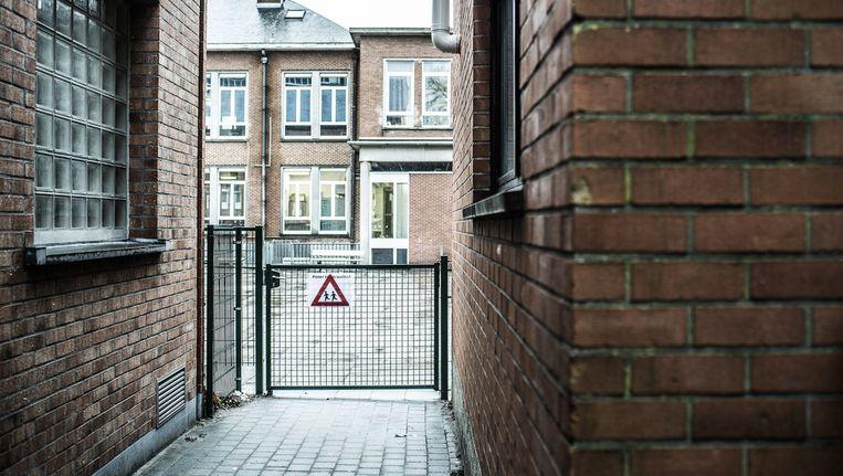 Het hekje symboliseert de taalgrens in deze Brusselse school. Het moet te allen tijde gesloten blijven. Beeld Franky Verdickt