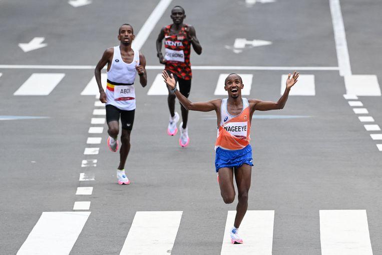 Abdi Nageeye gaat als tweede over de finish van de olympische marathon. Links de Belg Bashir Abdi, ook geboren in Somalië, die dankzij de aanmoedigingen van zijn vriend Nageeye net genoeg kracht bij elkaar schraapte om brons te winnen. Beeld AFP