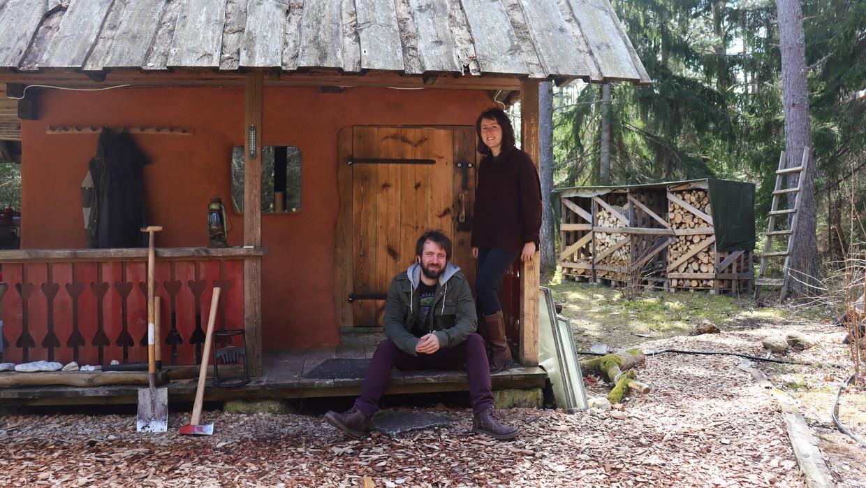 Jonas en Laura voor hun cabine in Estland: 'Onze vaste kosten zijn laag.We halen water uit een put, elektriciteit uit zonnepalen en we gaan groenten en bloemen kweken.' Beeld rv