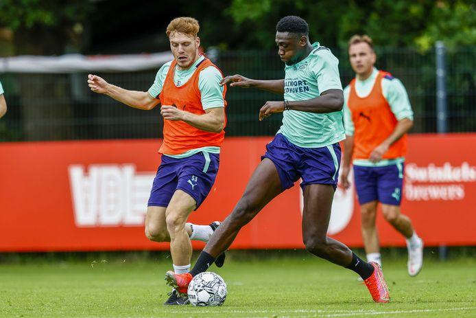 Derrick Luckassen in duel met Yorbe Vertessen tijdens het trainingskamp van PSV 1 in Duitsland, vorige maand.