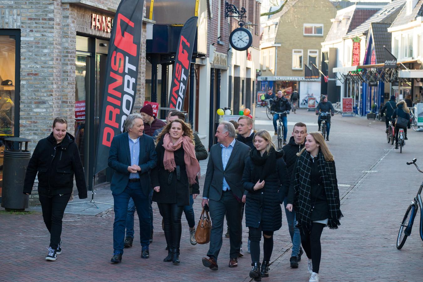 Alfa-studenten wandelen met centrummanager Eduard Plate (links) en lector Alexander Grit door het winkelcentrum.