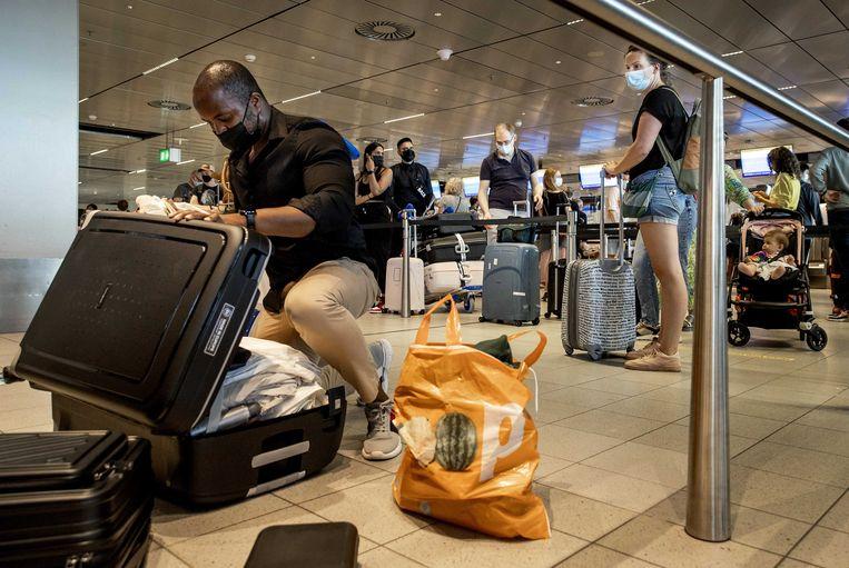 Reizigers wachten bij de incheckbalie op luchthaven Schiphol.  Beeld ANP
