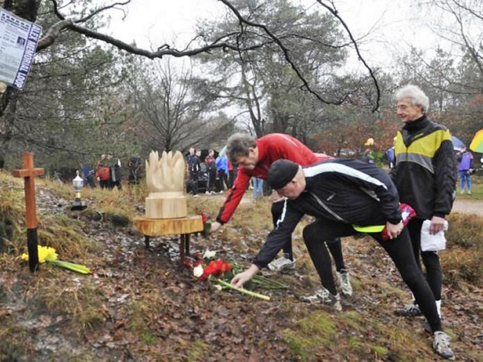 Hardlopers leggen bloemen bij een houtsculptuur op de Posbank, ter nagedachtenis aan Alex Wiegmink.