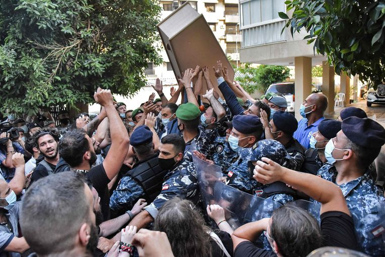 Veiligheidsdiensten slaan hard in op nabestaanden die met grafkisten naar het huis van Mohamed Fehmi lopen.  Beeld AFP