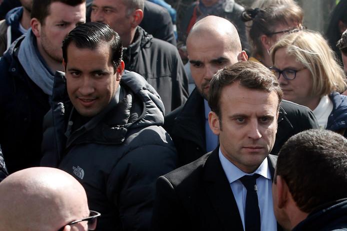 Alexandre Benalla, hier links op de foto te zien met zwarte jas met capuchon.