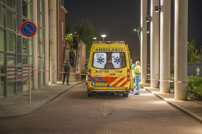 Hulpverleners bij een appartement aan de Goudbaard in Bergen op Zoom, waar een vrouw is overleden na een geweldsincident. De politie is nog op zoek naar de verdachte.