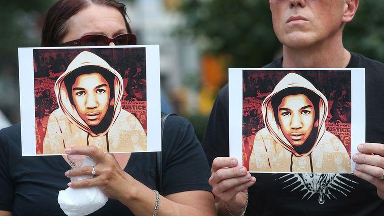 Demonstranten in New York houden een foto vast van Trayvon Martin. Ze protesteren tegen de vrijspraak van Zimmerman. Beeld GETTY