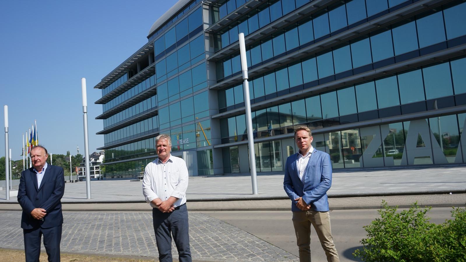 Luc Michiels, CEO van Umisol, schepen Hugo Maes en installateur Stijn Sillis bij AC De Zaat. Alle glaspartijen langs de zuid- en oostkant kregen een speciale folie.