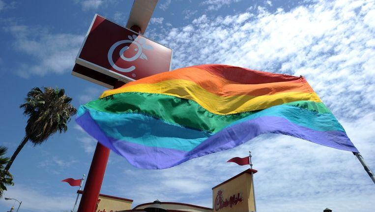 Een regenboogvlag wordt voor de deur van een Chick-fil-A restaurant omhoog gehouden. Beeld afp