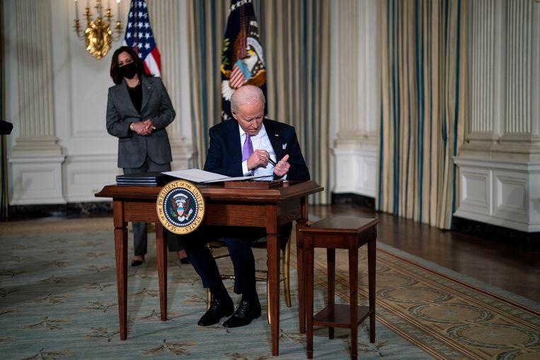 Onder toeziend oog van vicepresident Kamala Harris ondertekent president Joe Biden een stapel decreten in een zaal van het Witte Huis.   Beeld Doug Mills / EPA