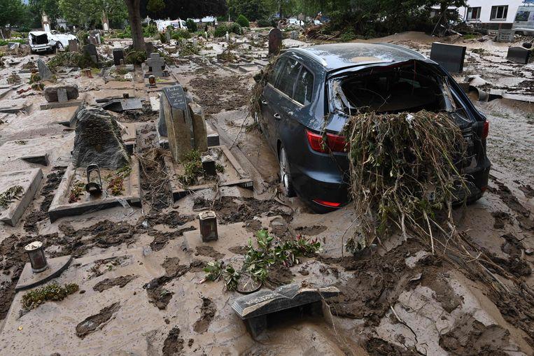 Een door het water verwoeste auto op een overspoelde begraafplaats in Bad Neuenahr-Ahrweiler. Beeld AFP