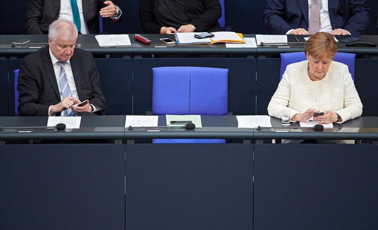 Minister van binnenlandse zaken Horst Seehofer en bondskanselier Angela Merkel in het Duitse parlement. Beeld EPA