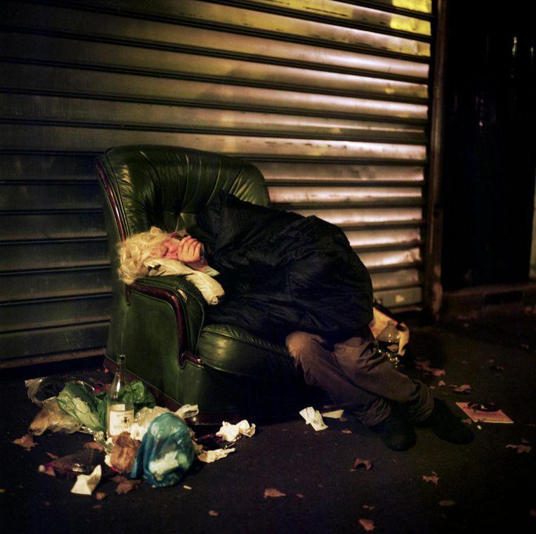 Frankrijk, Parijs, 08 december 2015, dakloze man schuilt onder een afdakje voor de regen en de kou. Beeld null