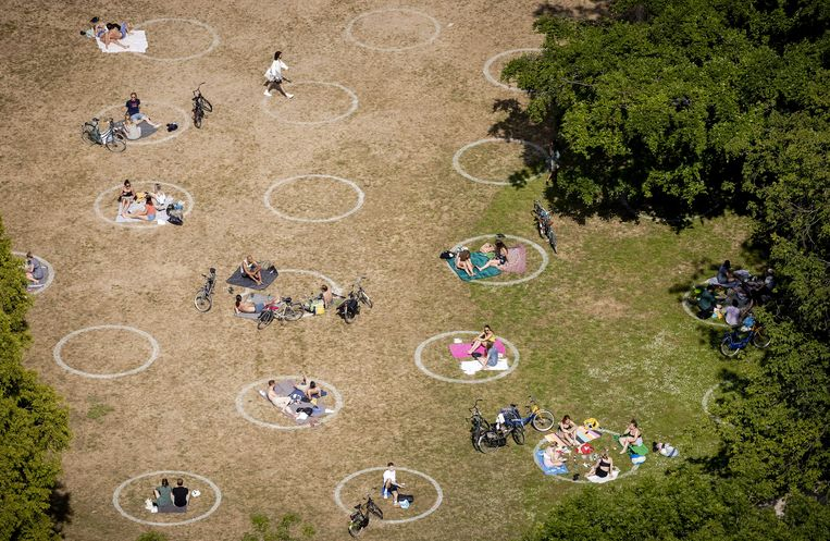 Mensen genieten van de zon in het Rotterdamse Vroesenpark, het park bij de Euromast.  Beeld ANP