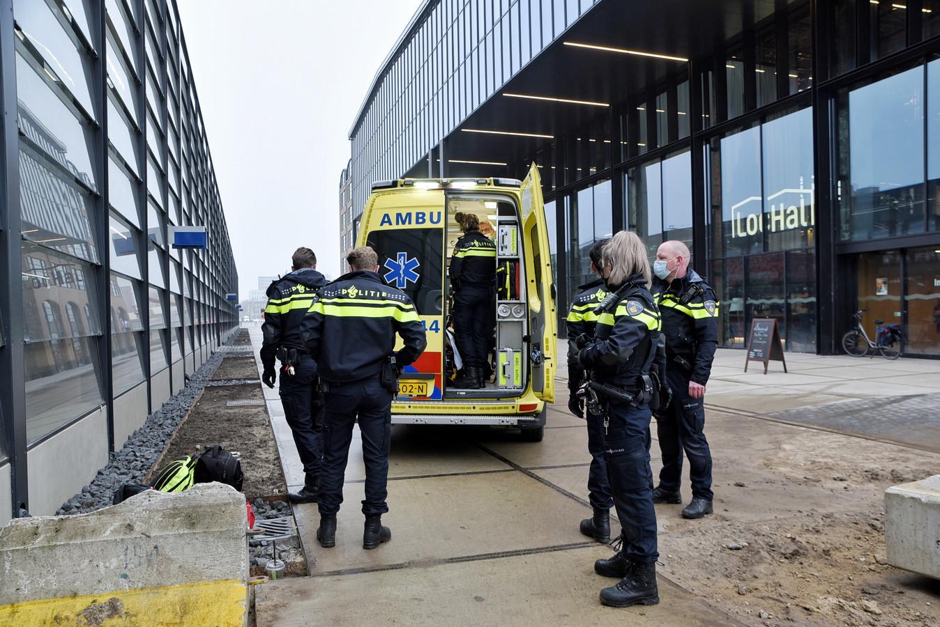 De man wordt, onder begeleiding van een agent, meegenomen in een ziekenwagen.