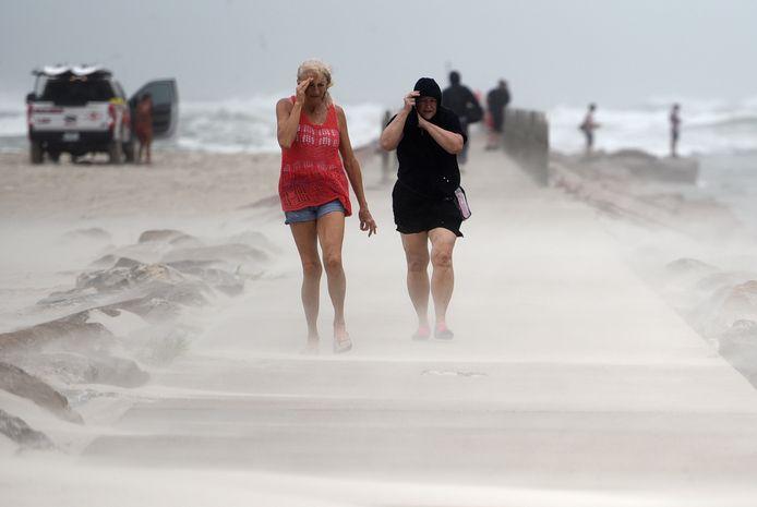 Mensen schermen hun gezichten af voor het opstuivende zand op het strand in Corpus Christi, Texas, dat in lijn van storm Nicholas ligt.