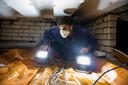 Emrah, monteur van het bedrijf Tonzon, is in een kruipruimte bezig met de installatie van vloerisolatie