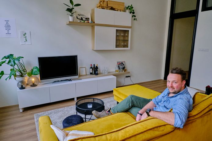 """Robin Gommers (30) in zijn appartement in het oude Zeeman-pand. De bank heeft hij op de kop getikt via Instagram. ,,Ik vind okergeel een supertoffe kleur."""""""
