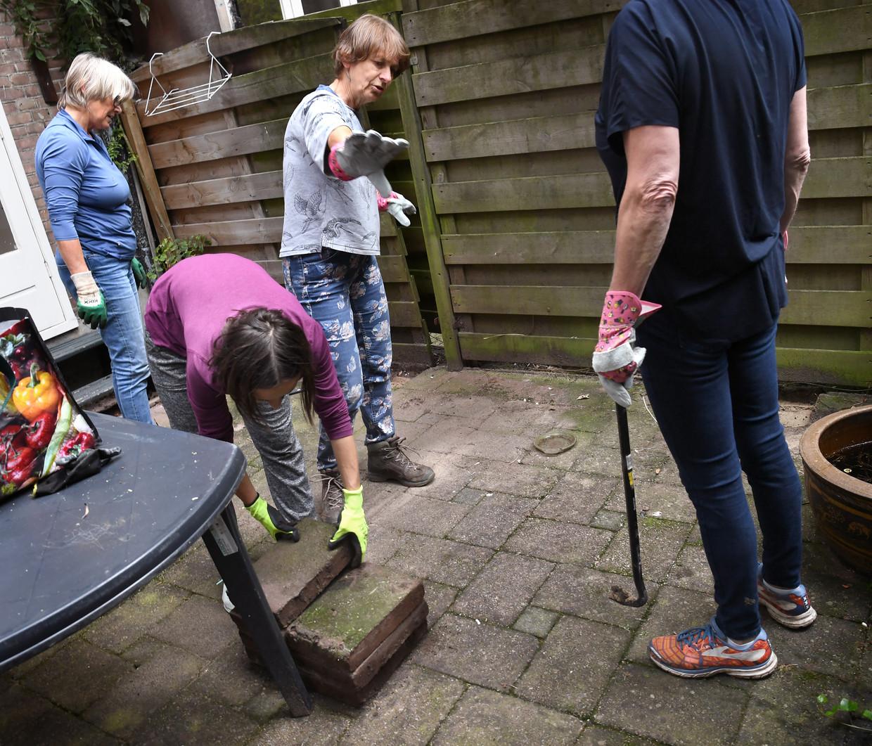 Luella van Turnhout (midden), kartrekker van het project GroeneBuurten, pakt met haar 'tegellichters' een tuin in Amsterdam aan. Beeld Marcel van den Bergh / de Volkskrant